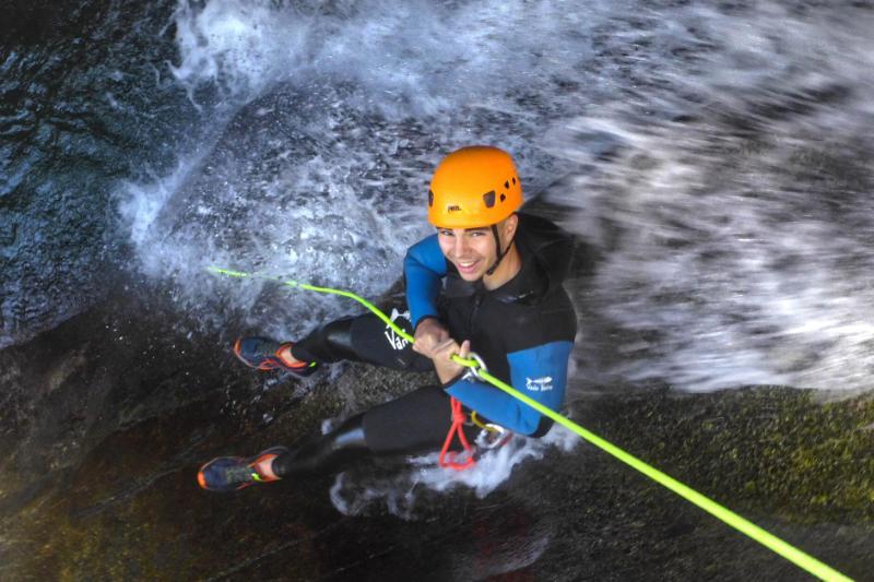 Une personne descend une cascade en rappel