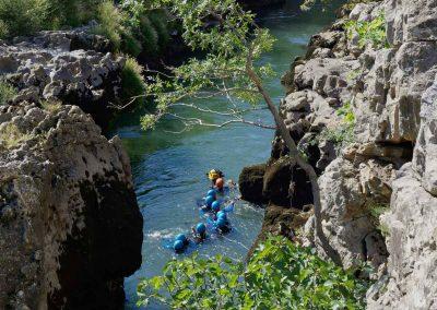 Un groupe de canyoning descend une rivière.