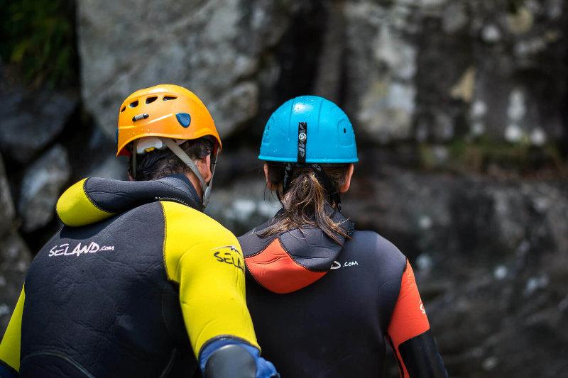 Un moniteur de canyoning donne des consignes à une cliente avant un saut