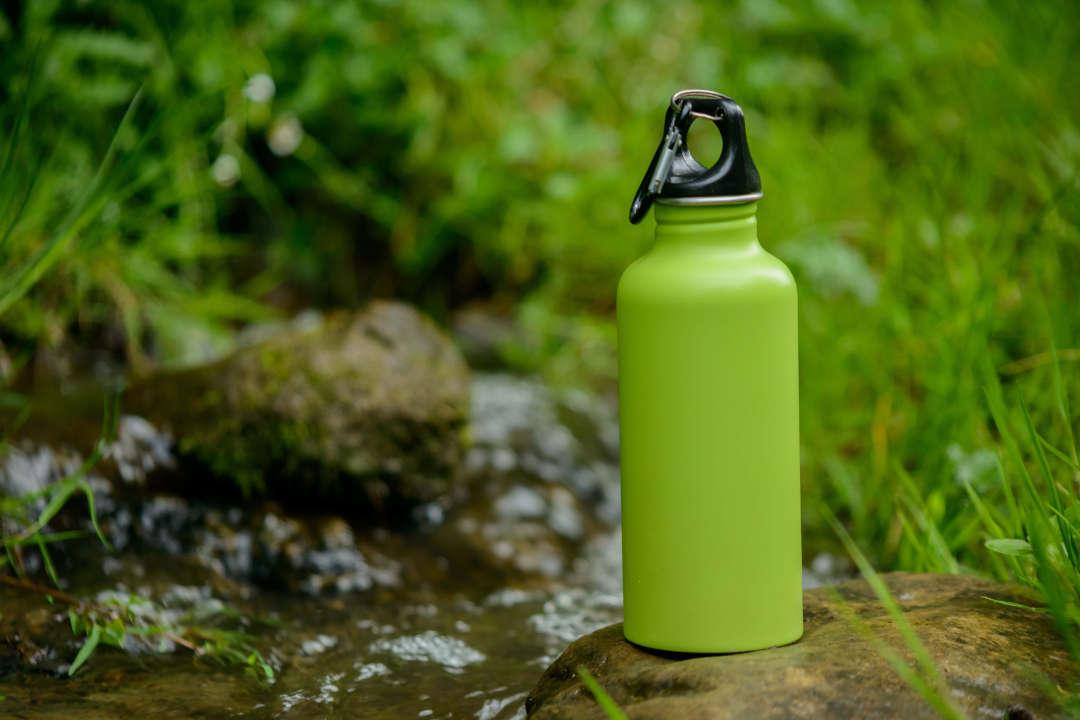 Gourde verte en inox sur un rocher dans la nature