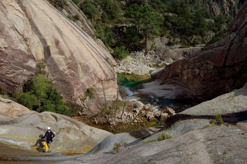 Un canyoniste descend en rappel dans le canyon de Purcaraccia en Corse