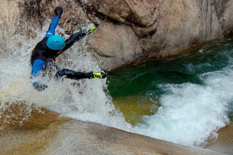 Un canyoniste fait un saut lors d'un toboggan dans le canyon de Purcaraccia en Corse
