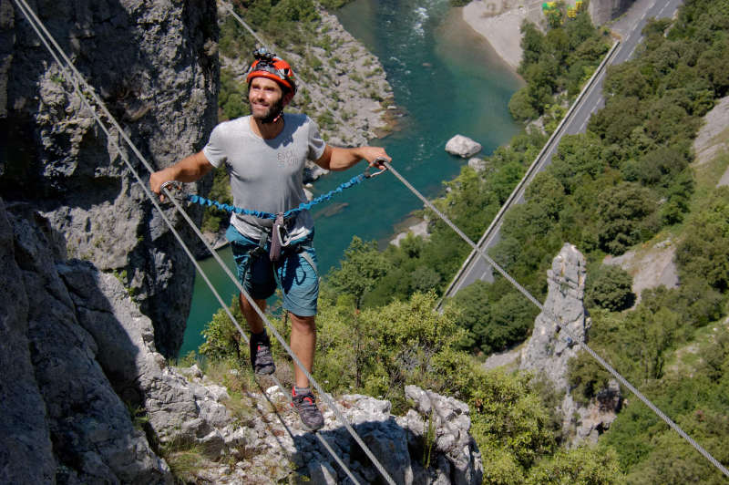 Person on a cable suspended bridge over the Herault river