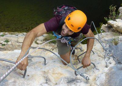 Personne grimpant des barreaux dans la via ferrata du Vidourle à Saint-Sériès
